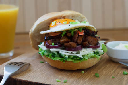Big chicken burger on brown wooden background. Imagens