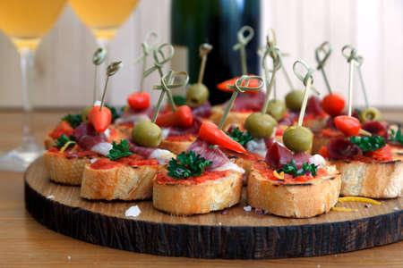 tapas españolas: Tapas en el pan crujiente - La selección de tapas españolas que se presentan en una barra de pan en rodajas Foto de archivo