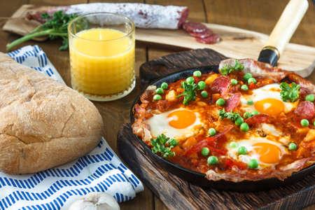 Spanish cuisine. Eggs on vegetables, Andalusian style. Huevos a la flamenca