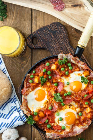baked eggs with chorizo, potatoes and tomatoes in a pan on the table. close up top view, vertical