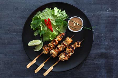 Kipsate of Sate Ayam - Maleisische beroemde voedsel. Saté, moderne Indonesische en Maleisische spelling van sate, is een gerecht van doorgewinterde, spies en gegrild vlees, geserveerd met een pindasaus. bovenaanzicht
