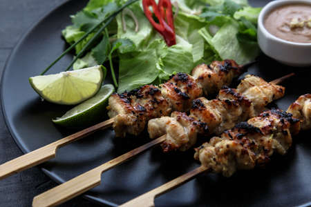 chicken satay: chicken satay with peanut sauce, indonesian skewer food, close view. Stock Photo