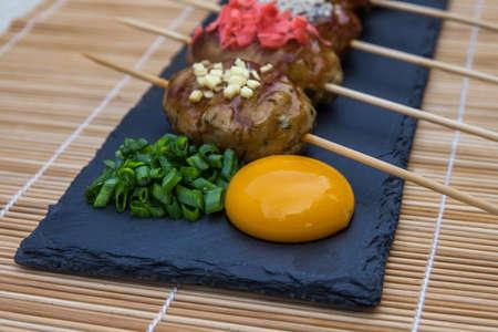 Tsukune - albóndigas de pollo yakitori japonés servido con salsa de chile, hojuelas de chile, pimienta molida y rodajas de limón.
