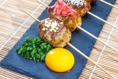 Tsukune - Japanese chicken yakitori meatballs served with chili sauce, chili flakes, ground pepper and lemon wedges.