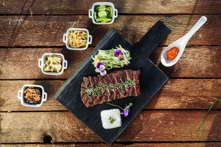 side dishes: Korean BBQ with full side dishes on wooden background