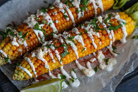yellow corn: Grilled corn cobs on wooden plate, mexican style, close view.