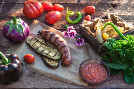 Grilled sausages and vegetables in rustic style. Selective focus