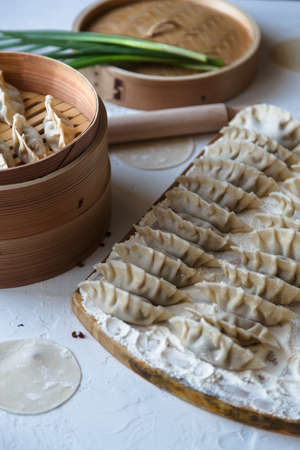 potstickers: Raw Homemade Chinese Dumplings on Wooden Board.