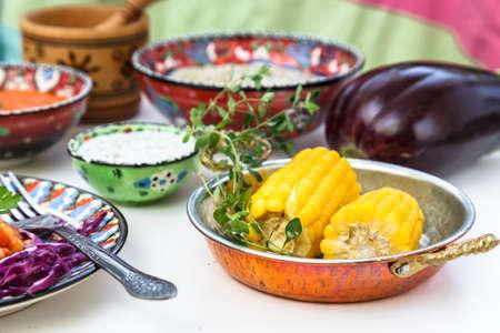 Corn elotes in copper pan. Mediterranian meze