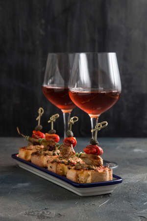 spanish tapa pinxtos with tuna, peper, onion and oregano. Wine on background.