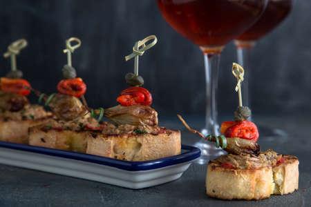 FOODIES:  Pintxos Tapa on traditional plate, crispy bread, tuna, onion and pepper. Stock Photo