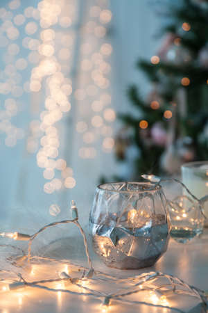 Candle holder with christmas lights and atmospheric light on background. Stock Photo