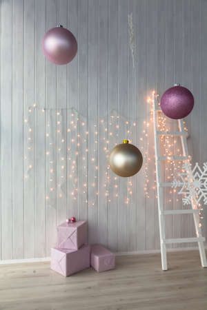 christmas lights burning on a white wooden background with pink giftboxes and stairs stock photo