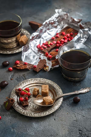 Chocolate bar with dry berries on silver vintage plate, close view, dark background Stock Photo