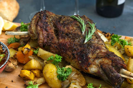Roast lamb shoulder with baked vegs, close view.