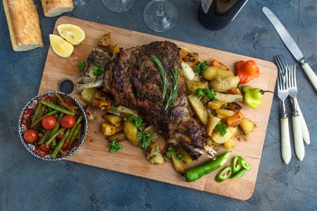 Roast lamb shank with roasted potatoes and carrots styled in a rustic wooden board, top view
