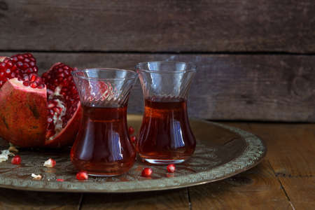 A glasses of pomegranate juice with fresh pomegranate fruits on wooden table. Vitamins and minerals. Healthy drink concept. Stock Photo