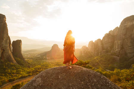 Girl in red flying dress looking at majestic sunset in Meteora valley, Greece.