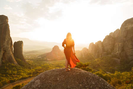 Young woman in red dress looking at majestic sunset in Meteora valley, Greece.