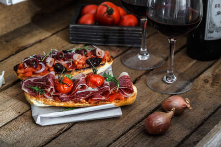 Tapas on crusty bread with red wine Stock Photo