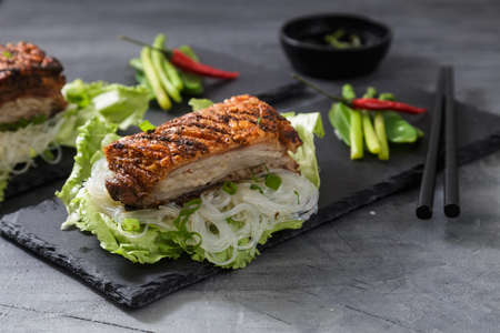 rou: Oriental Roast Pork Belly with crispy skin with greens and noodles Stock Photo