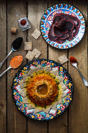ample: Spicy lentil dip with rusks and spices on arabian plate and wooden background background, top view.
