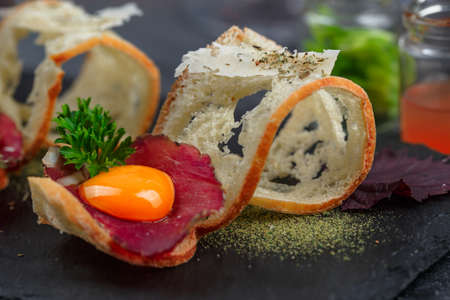 charcutería: Cured meat on crusty bread with yolk and parmegano cheese, close view, selective focus
