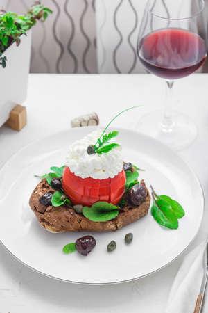 Dakos barley rusk with mizitra cheese, tomato, olives, oregano and olive oil. Cretan appetizer Stock Photo