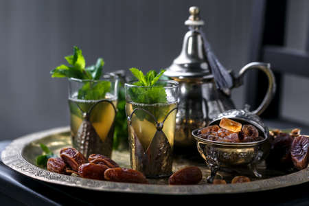 Moroccan tea with mint in traditional glasses, teapot and sugar