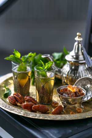 Moroccan tea with mint in traditional glasses, copper teapot on a copper plate