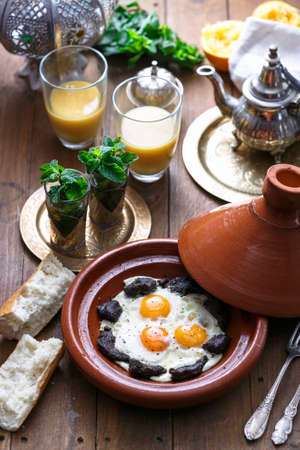 Sunnyside Eggs cooked in a Tajine dish with beef, Moroccan breakfast with juice and mint tea Stock Photo