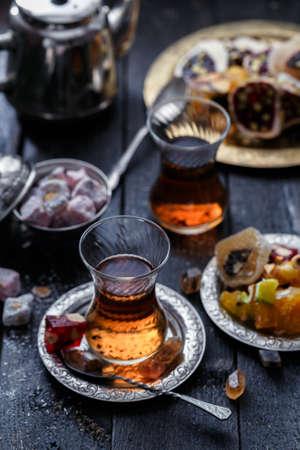 Turkish tea with sweets on dark background