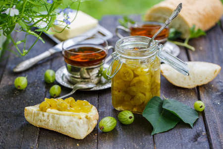 Jar with gooseberry jam on a wooden table Stockfoto