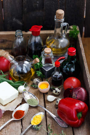 Olive oil, soy sauce, vinegar, infusions, butter and spices in a wooden box