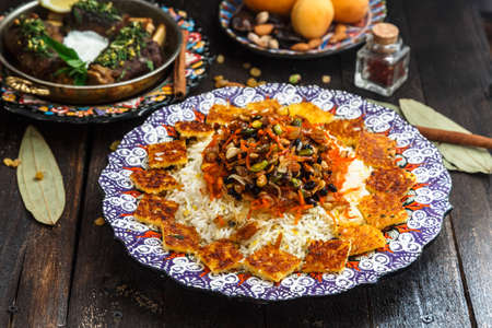 Delicious Iranian jewelled rice topped with nuts, raisins and orange zest