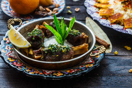 Baked lamb shanks middle eastern style in copper pan. Stock Photo