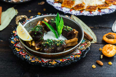 Lamb shanks with yoghurt and mint in a pan. Stock Photo