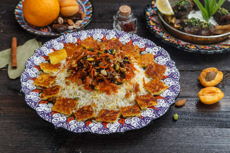 Iranian pilaf with orange zest, nuts and raisins, on a traditional plate Stock Photo