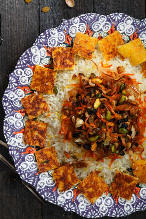 Iranian jewelled rice topped with orange zest, nuts and raisins in traditional plate