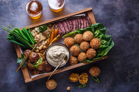 Middle eastern party food: falafel, babaghanoush, potatoes, beef, green veggies.