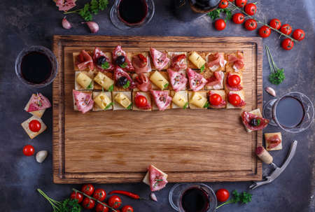 Wooden board with pinxtos or tapas with jamon, ham and sausage, flat lay.