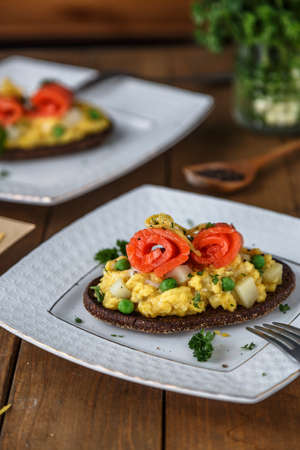 Smorrebrod with salmon and scramble egg on rye bread