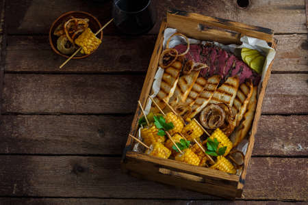 Sliced beef pastrami with grilled corn, copy space