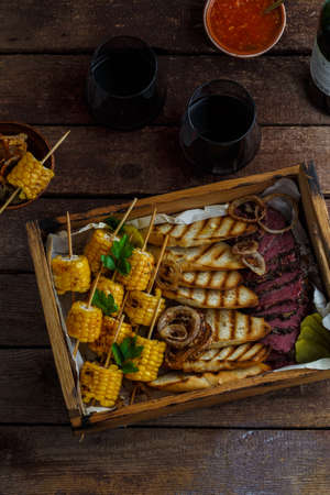 Smoked pastrami slices with grilled corn and wine.