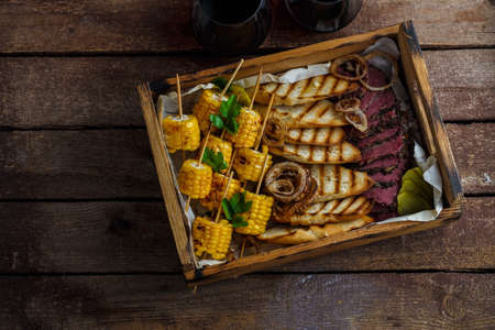 Grilled corn, sliced pastrami and toasted bread with wine, top view copy space.