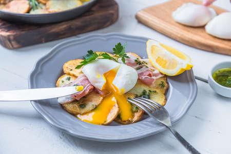 Running eg yolk on poached eg over potato and jamon Banco de Imagens