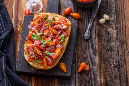 Italian bruschetta with prosciutto, tomato and basil, copy space.