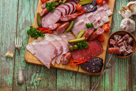 Charcuterie board with sausages and smoked meat. Top view. Фото со стока