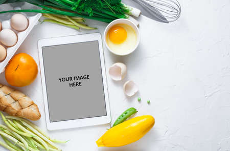 Cooking recipes on tablet with vegetables on background, copy space Standard-Bild
