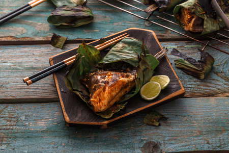 Sambal stingray in a leaf on a wooden board, malaysian cuisine, copy space